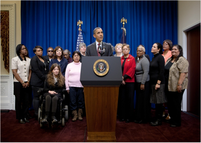 Gilda Brown, far left, stands with President Obama and other home care workers and consumers as he announces new overtime and minimum wage protections for home care workers.