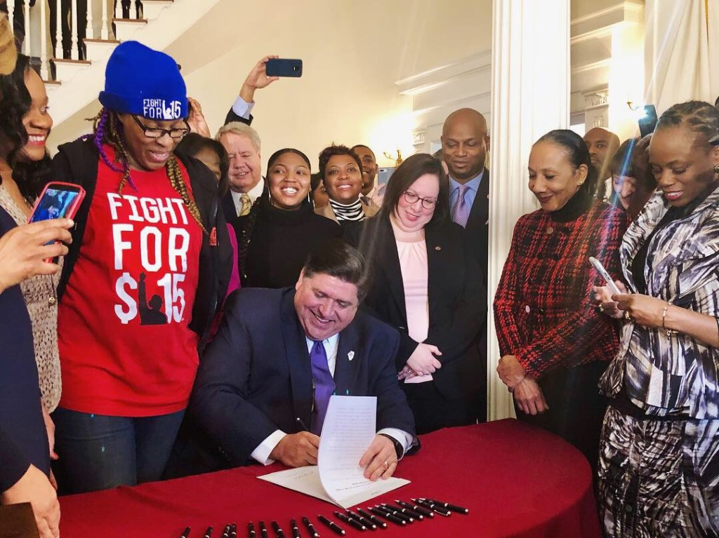Feb. 19th, 2019, Gov. J.B. Pritzker signs historic bill to raise Illinois minimum wage to $15 an hour by 2025. Standing behind him is Tichina Haywood, a CNA earning $12.67 an hour whom Pritkzer said he would recognize her when he signed the bill.